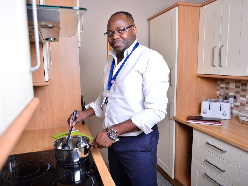 SETTLED-CARE-Moses-cooking-smiling-at-camera